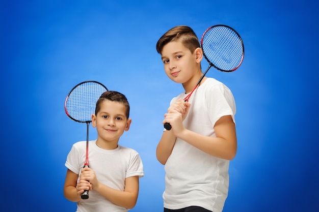 De twee jongens met badmintonrackets buiten Gratis Foto