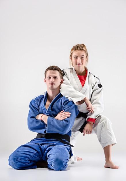 De twee judoka's strijders poseren op grijs Gratis Foto