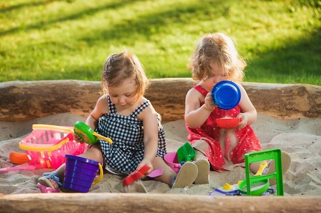 De twee kleine babymeisjes die speelgoed in zand spelen Gratis Foto