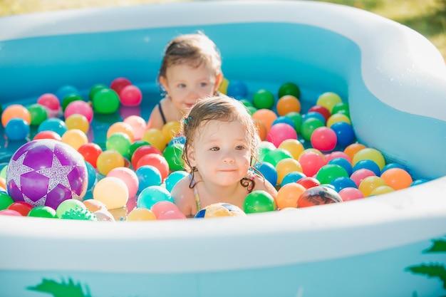 De twee kleine babymeisjes spelen met speelgoed in opblaasbaar zwembad in de zonnige zomerdag Gratis Foto