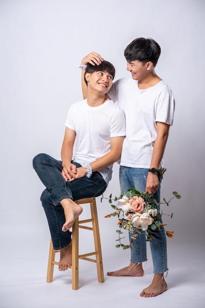 De twee mannen die van elkaar hielden, hielden hun hoofd vast en gingen op een stoel zitten. Gratis Foto