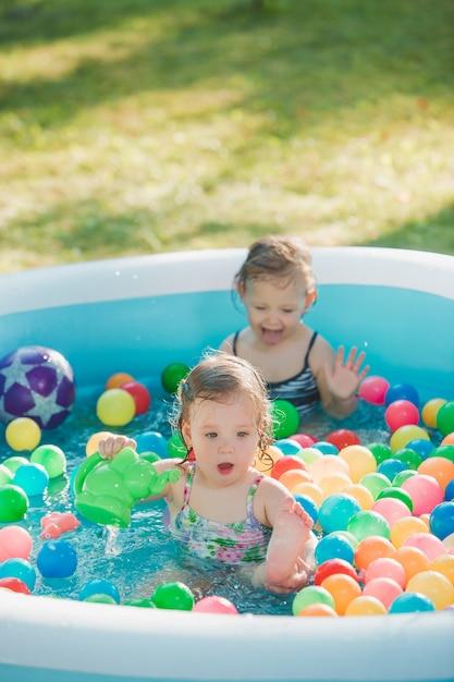 De twee twee jaar oude kleine baby meisjes spelen met speelgoed in opblaasbaar zwembad in de zonnige zomerdag Gratis Foto