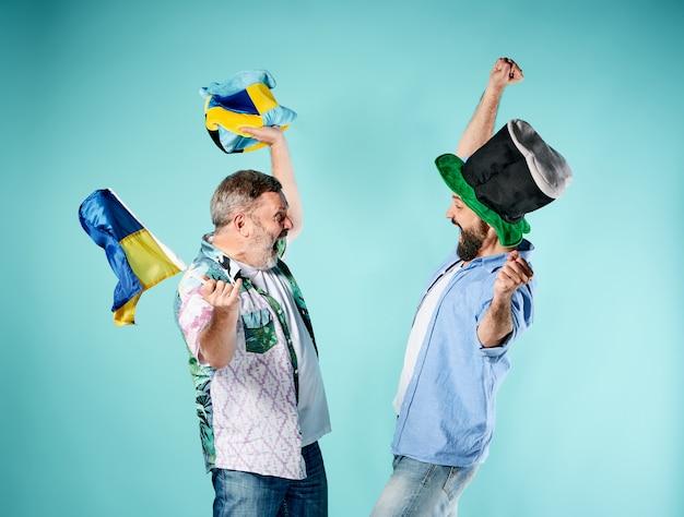 De twee voetbalfans met een vlag van oekraïne over blauw Gratis Foto