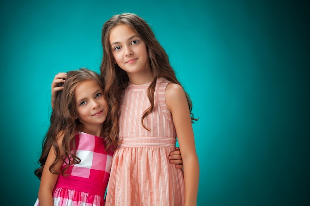De twee vrolijke kleine meisjes op blauwe muur Gratis Foto