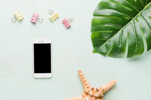 De vakantiesamenstelling van het strand met telefoon op lichte achtergrond Gratis Foto