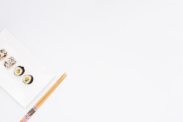 De verfraaide sushi rolt op plaat en eetstokjes over witte achtergrond met ruimte voor tekst Gratis Foto