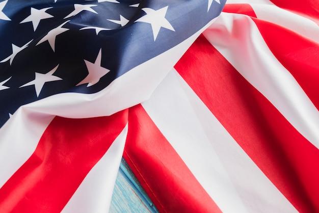 De verfrommelde vlag van de vs op blauwe houtoppervlakte Gratis Foto