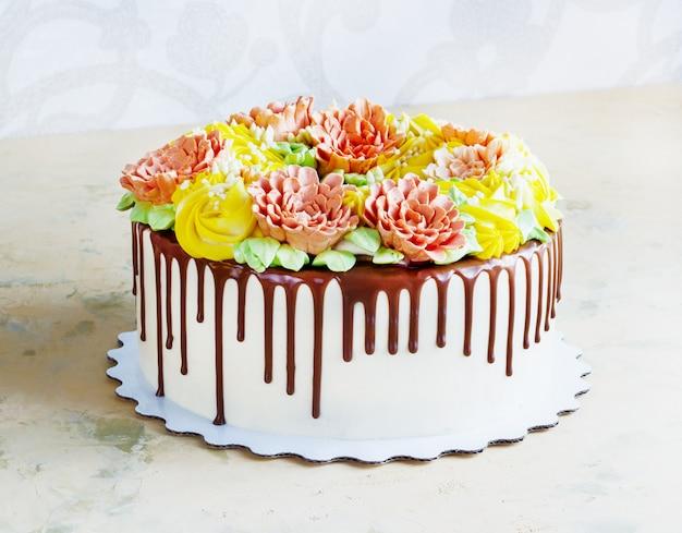 De verjaardagscake met bloemen nam op wit toe Premium Foto