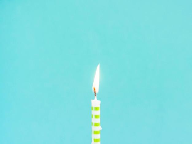 De verjaardagskaars van de close-up op blauwe achtergrond Gratis Foto
