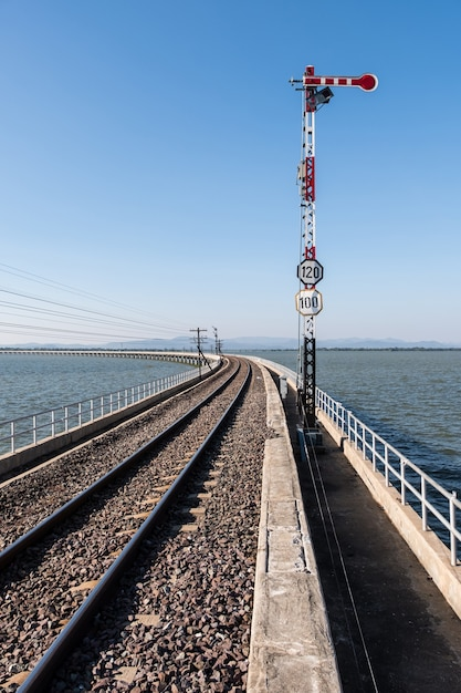 De verkeerslichtpaal in het stopsignaal van het spoorwegsignaleringssysteem op de gebogen betonnen brug Premium Foto