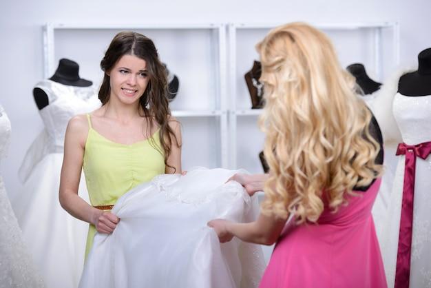 De verkoper geeft de blonde een nieuwe witte jurk. Premium Foto