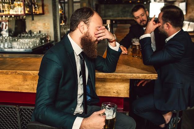 De vermoeide jonge man zit en behandelt gezicht met hand. twee andere mannen zitten achter en praten. ze zijn in de bar. Premium Foto