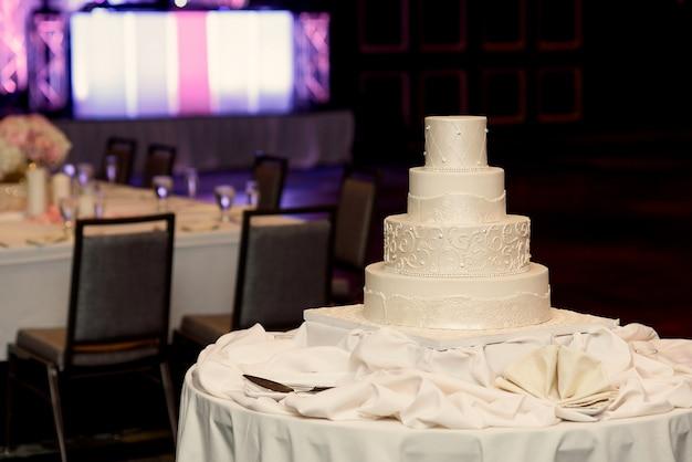 De vermoeide witte huwelijkscake bevindt zich op de zijdedoek in een diner Gratis Foto