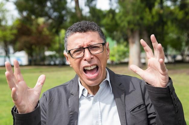 De verontwaardigde mens die op middelbare leeftijd en opheft schreeuwt en heft park op Gratis Foto