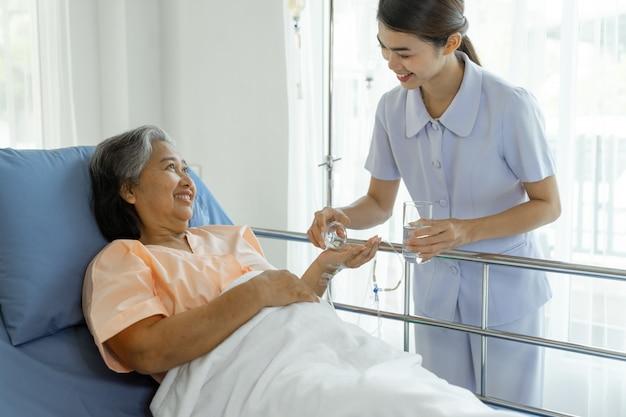 De verpleegkundigen zijn goed verzorgd en geven medicijnen aan oudere patiënten in ziekenhuisbedpatiënten voelen zich gelukkig - medisch en medisch senior patiëntconcept Gratis Foto