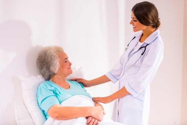 De verpleegster kwam het oude meisje in bed bezoeken. Premium Foto