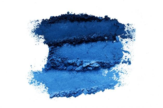 De verpletterde die reeks van de oogschaduwmake-up op witte achtergrond wordt geïsoleerd. kleur van het jaar 2020 classic blue. Premium Foto
