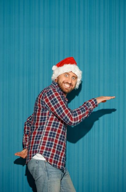 De verraste kerstman met een kerstmuts op de blauwe achtergrond Gratis Foto