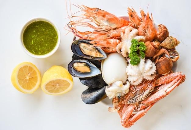 De verse garnalengarnalen van de garnalenpijlinktvis bevlekte babylon schaaldierenkrab en de citroen van de zeevruchtensaus op plaat witte achtergrond. Premium Foto