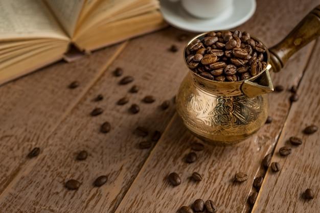 De verse geroosterde koffiebonen in cezve (traditionele turkse koffiepot) opende boek en kop op houten lijst. Premium Foto