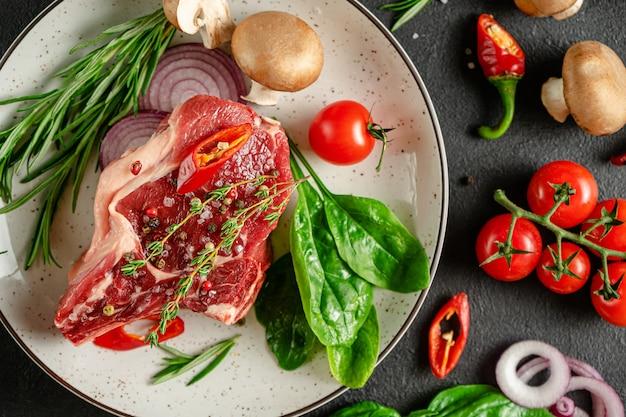 De verse lapjes vlees van het kalfsvlees op plaat met kruiden en specerijen. koken concept. plat lag, bovenaanzicht Premium Foto