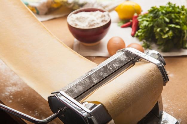 De verse pasta en machine op de keukentafel Gratis Foto