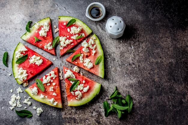 De verse salade van de watermeloenpizza met feta-kaas, munt, zout en olie op steen Premium Foto