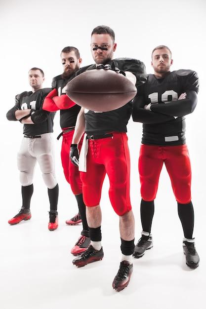 De vier blanke fitness mannen als amerikaanse voetballers poseren van volledige lengte met een bal op een witte achtergrond Gratis Foto