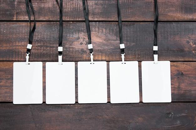 De vijf kaart badges met touwen op houten tafel Gratis Foto
