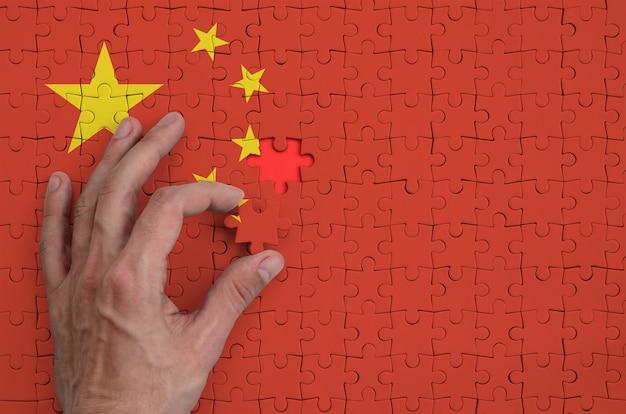 De vlag van china is afgebeeld op een puzzel, die de hand van de man voltooit om te vouwen Premium Foto