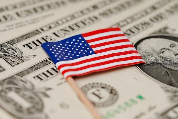De vlag van de vs amerika op de achtergrond van dollarbankbiljetten. Premium Foto