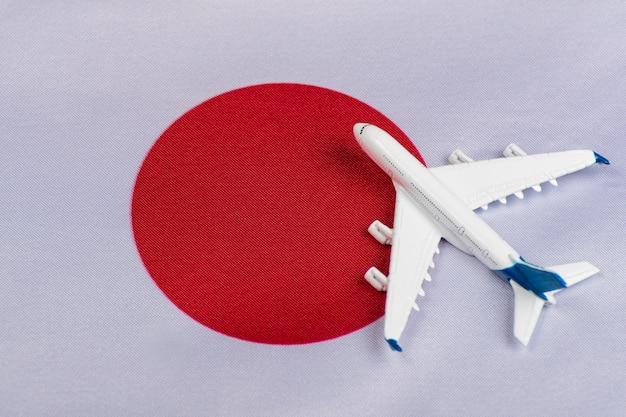 De vlag van japan en stuk speelgoed vliegtuig dichte omhooggaand Premium Foto
