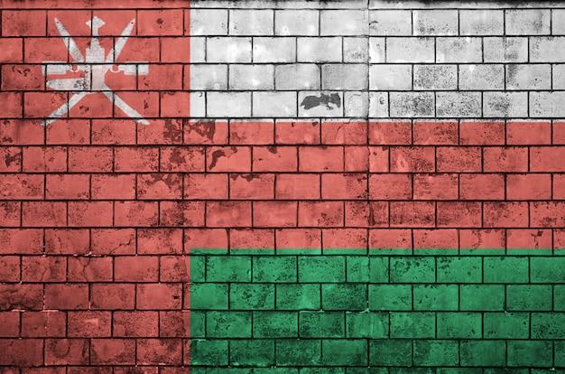 De vlag van oman is op een oude bakstenen muur geschilderd Premium Foto