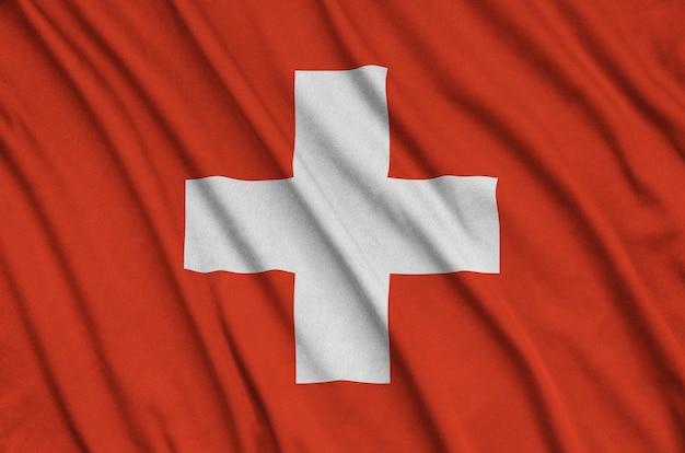 De vlag van zwitserland is afgebeeld op een sportdoek met veel vouwen. Premium Foto