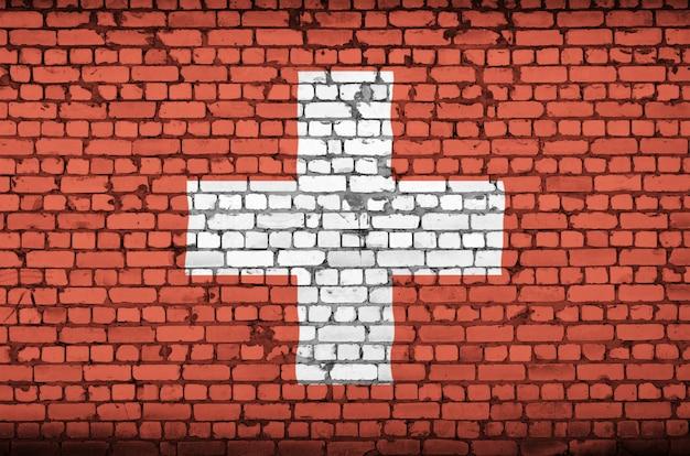 De vlag van zwitserland is op een oude bakstenen muur geschilderd Premium Foto