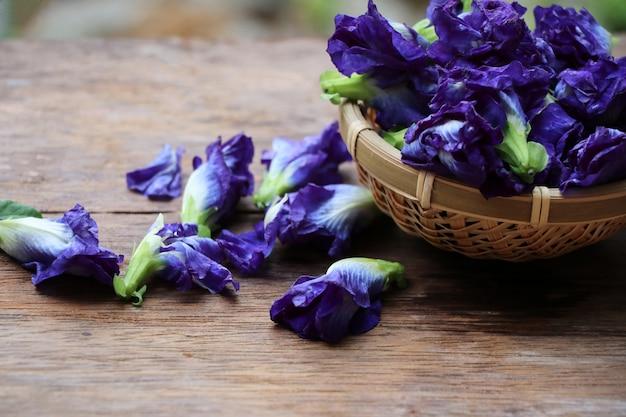 De vlindererwt bloeit blauwe kleur in de mand aziatische kruidenbloemen op houten achtergrond Premium Foto