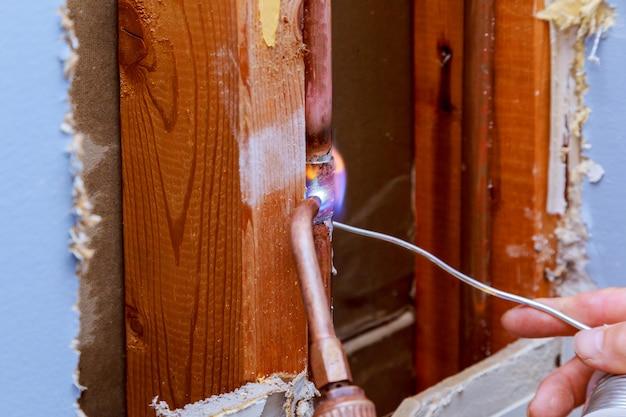 De vloeideeg van de close-up professionele hoofdloodgieter voor het solderen van koperpijpgasbrander het veranderen van flatgebouwpijpleiding, lekkage Premium Foto