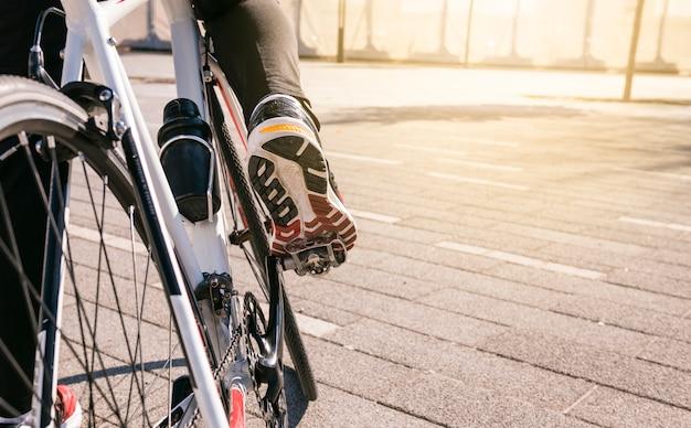 De voet van de mannelijke fietser op fiets pedaal berijdende fiets in openlucht Gratis Foto
