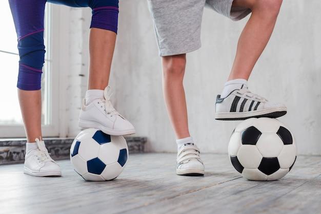De voet van het meisje en van de jongen op voetbalbal Gratis Foto