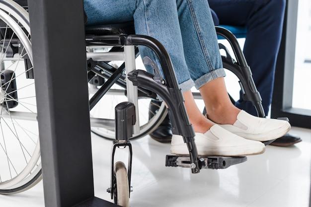 De voeten van de gehandicapte vrouw op rolstoel op witte vloer Gratis Foto