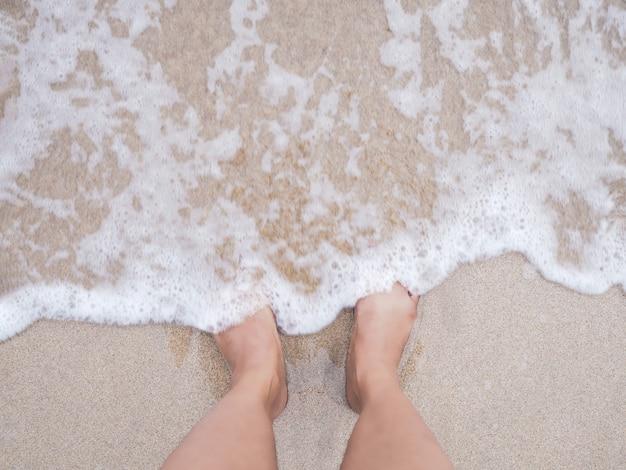 De voeten van de selfievrouw op de achtergrond van het de zomerstrand. Premium Foto
