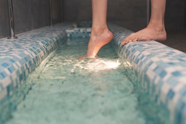 De voeten van de vrouw op de rand van badkuip Gratis Foto