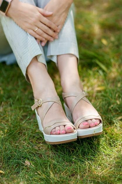 De voeten van een vrouw in zomerschoenen en gestripte broek die zich op het groene gras bevinden Premium Foto