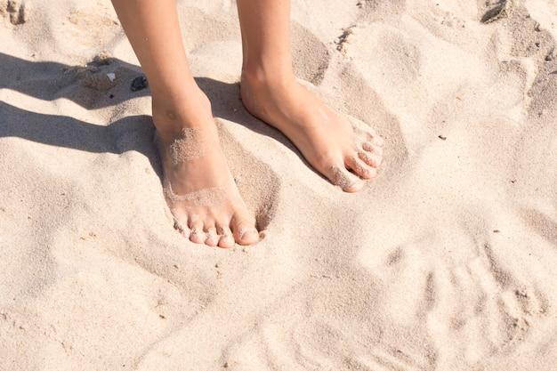 De voeten van het kind in het zand Premium Foto