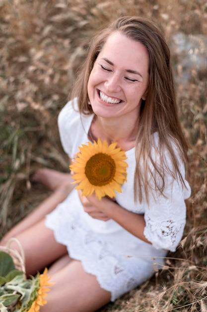 De volledig geschotene zonnebloem van de vrouwenholding Premium Foto