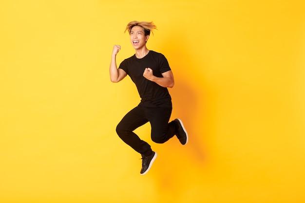 De volledige lengte van gelukkige aantrekkelijke aziatische kerel in zwarte kleren die en de overwinning springen vieren, doel bereiken, gele muur staan, zegevierend. Gratis Foto