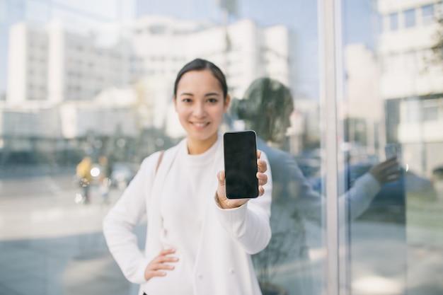 De volwassen aziatische mooie bedrijfsvrouw bevindt zich voor bureaucentrum dat het haar telefoonscherm toont Premium Foto