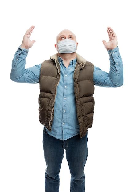 De volwassen kale mens in een medisch masker hief zijn handen op in gebed. de financiële crisis en quarantaine tijdens de pandemie van het coronavirus. voorzorgsmaatregelen Premium Foto