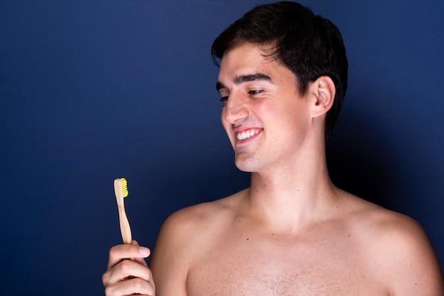 De volwassen mens die van smiley tootbrush houdt Gratis Foto