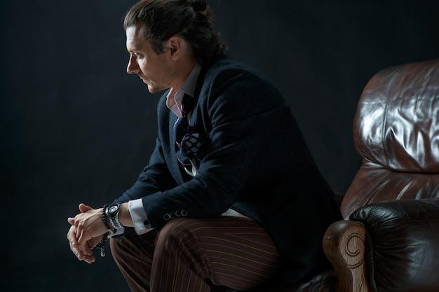 De volwassen stijlvolle man in een pak op een grijs. zakenmanzitting op een leunstoel Gratis Foto